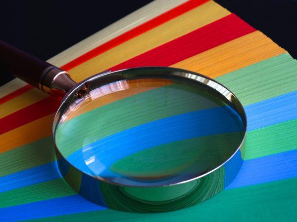 Imagen de una lupa con papeles de colores